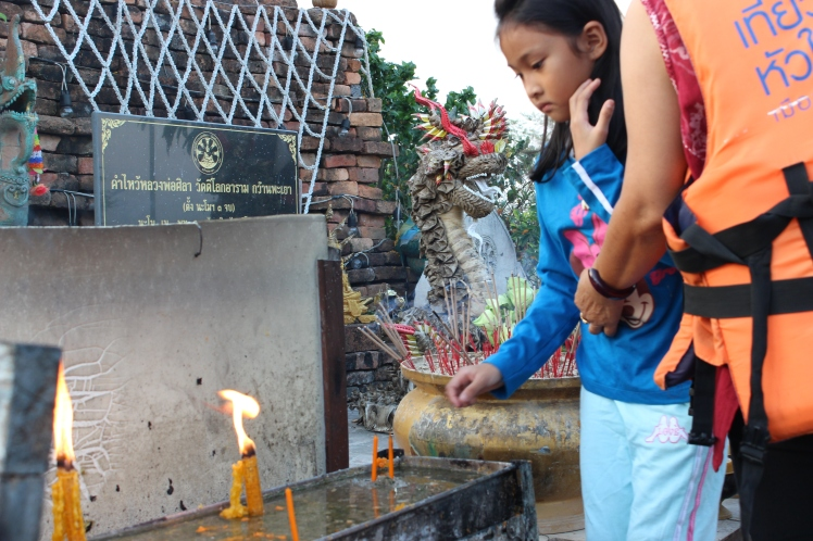 A young girl lighting incense before the Buddha statue.