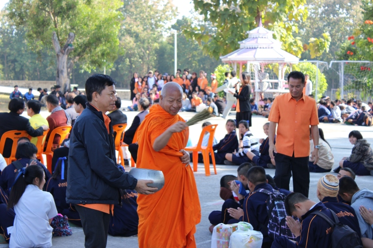 """A monk sprinkles """"holy water"""" over the students."""